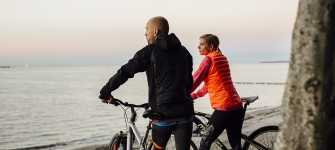 Cyclists enjoy the view over the Baltic Sea coast during a break, © TMV/Roth